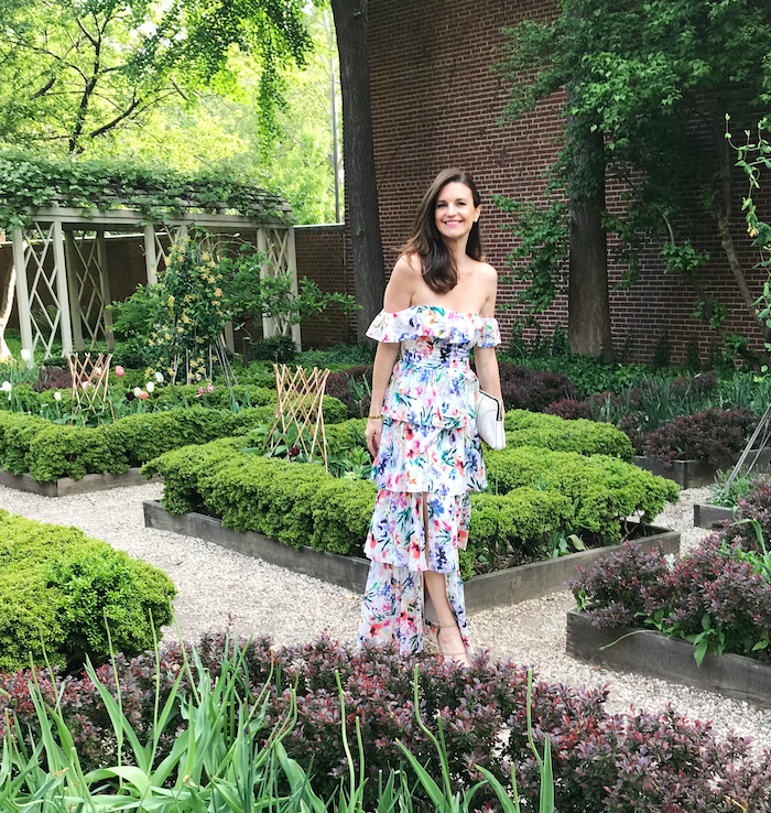wedding guest dresses brunette woman wearing strapless white dress with green pink blue purple flowers standing in a garden