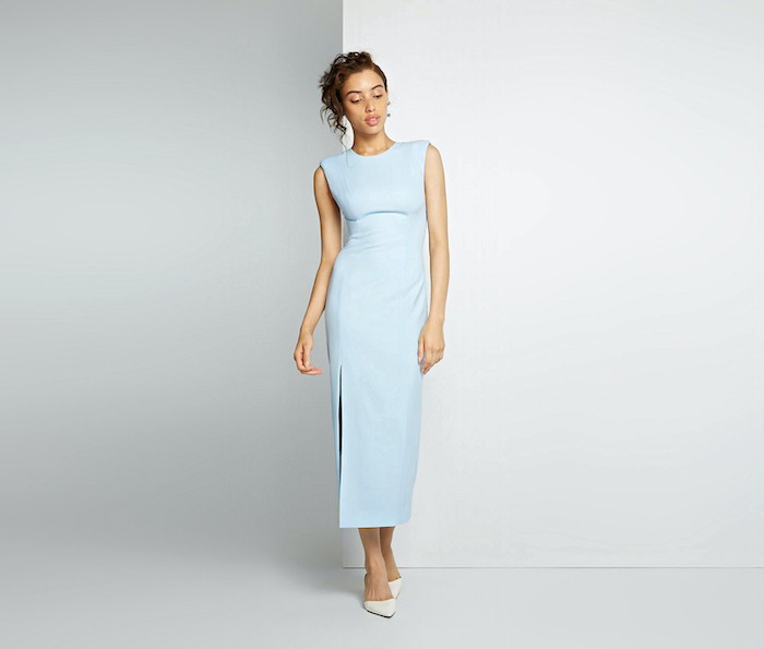 wedding guest outfits woman with brown hair in updo wearing blue dress white shoes photographed on white background