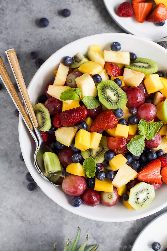 white bowl filled with fruits how to make salad kiwi strawberries blueberries grapes mango pineapple mint leaves