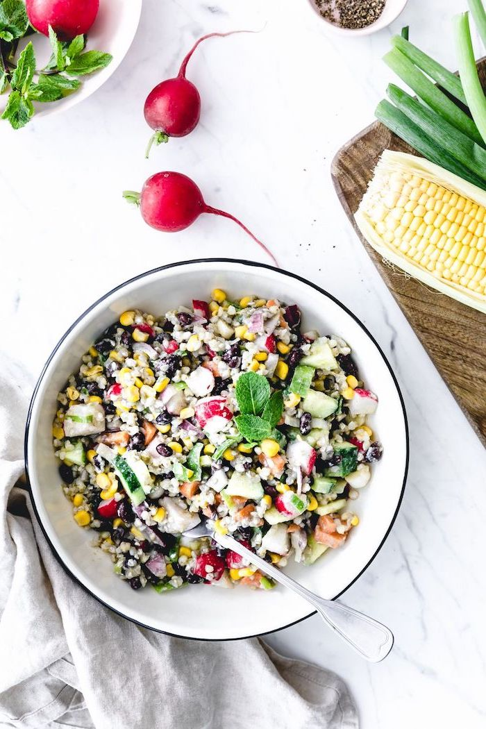 white metal bowl filled with corn salad with black beans summer salad recipes cucumbers onion fresh mint leaves on top