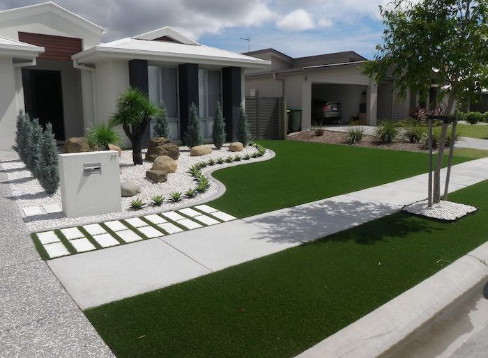 white one storey house cheap landscaping ideas grass and white tiles small gravel garden with bushes and small trees