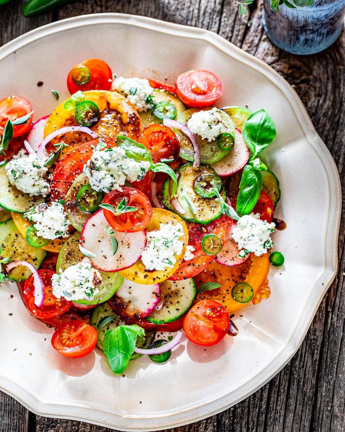 white plate with different types of salads ricotta salad with tomatoes cucumbers peppers turnip basil leaves for garnish