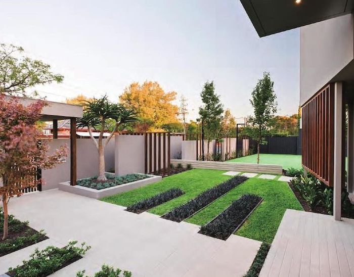 white tiled pathway surrounded by grass small front yard ideas small trees and flower beds on the sides