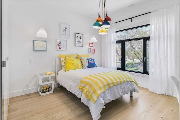 white walls wooden floor large window with white curtains teen boy bedroom furniture colorful lamps hanging from the ceiling
