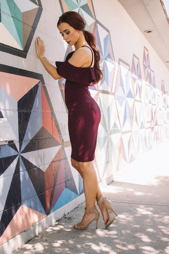 woman leaning on a wall wearing dark burgundy dress beach wedding guest dresses nude sandals with long wavy hair in low ponytail