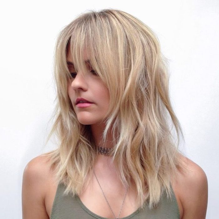 woman wearing green top short hairstyles for thin hair shoulder length blonde hair with highlights with bangs