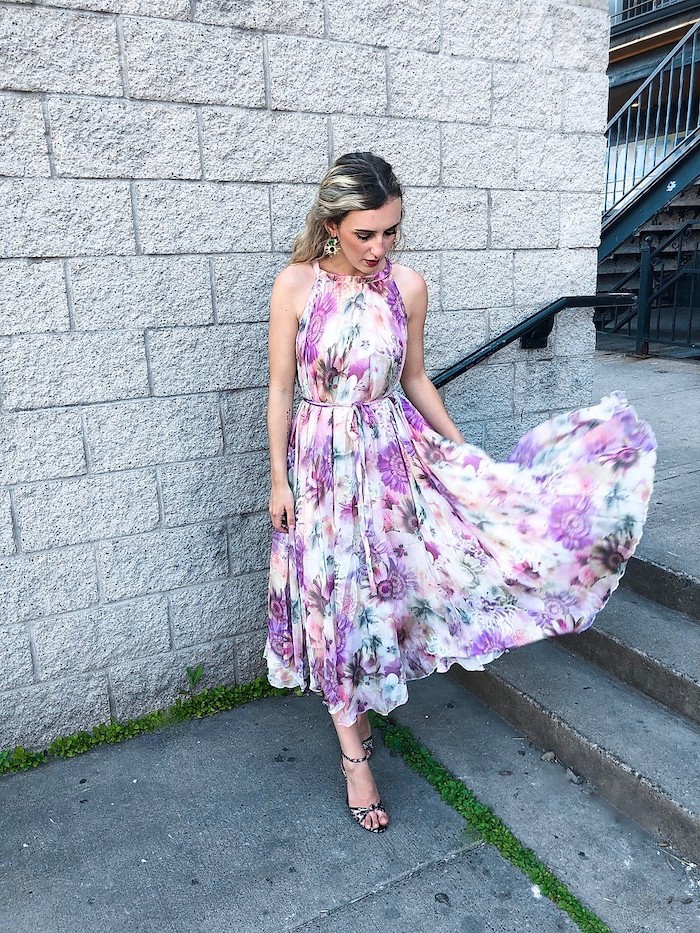 woman with balayage hair wearing midi white dress with purple flowers wedding guest dresses standing on staircase