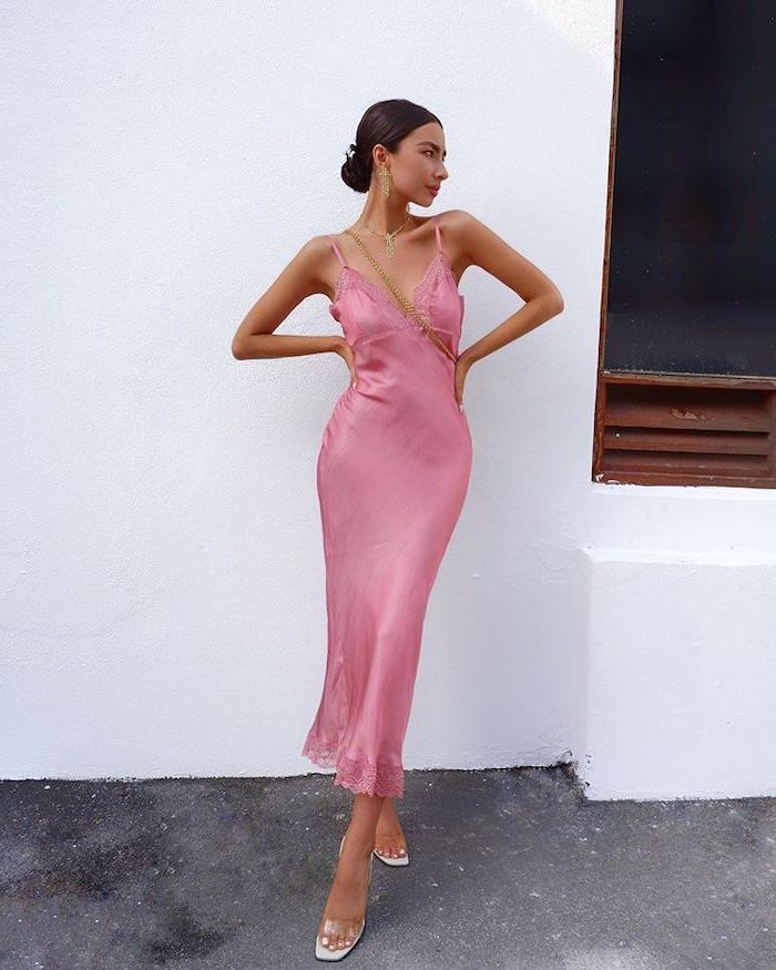woman with black hair in low updo wearing pink satin midi dress beach wedding guest dresses white sandals