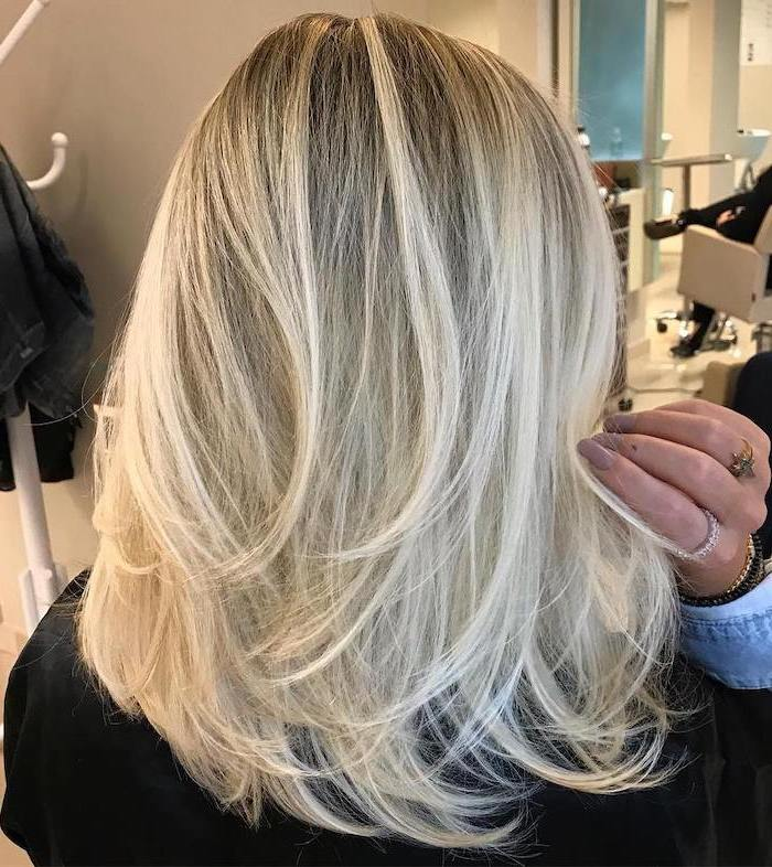 woman with blonde hair with blonde highlights hairstyles for medium hair long nails with beige nail polish
