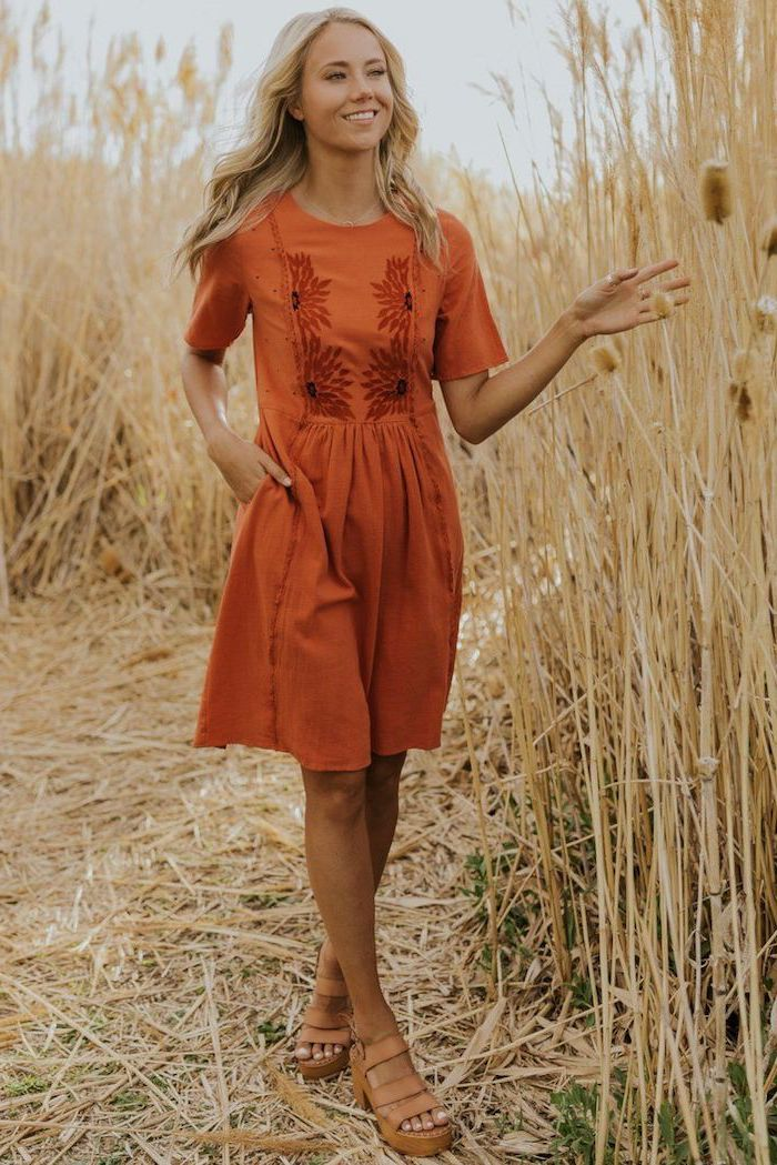 woman with long blonde wavy hair standing in a field flowy dresses wearing orange dress brown leather sandals