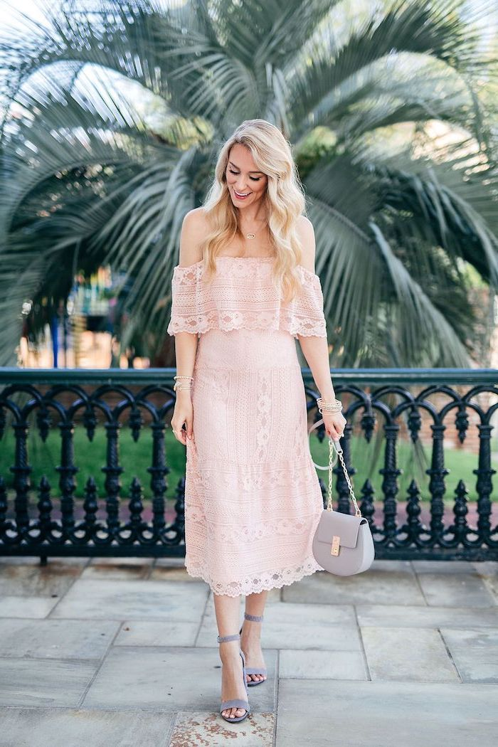 woman with long blonde wavy hair wedding guest dresses wearing strapless pink lace dress grey sandals leather bag