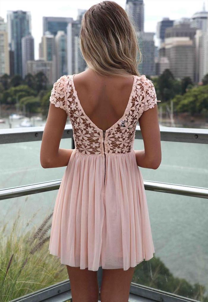 woman with long wavy hair wearing short pink dress with lace top summer dresses with sleeves standing on a balcony