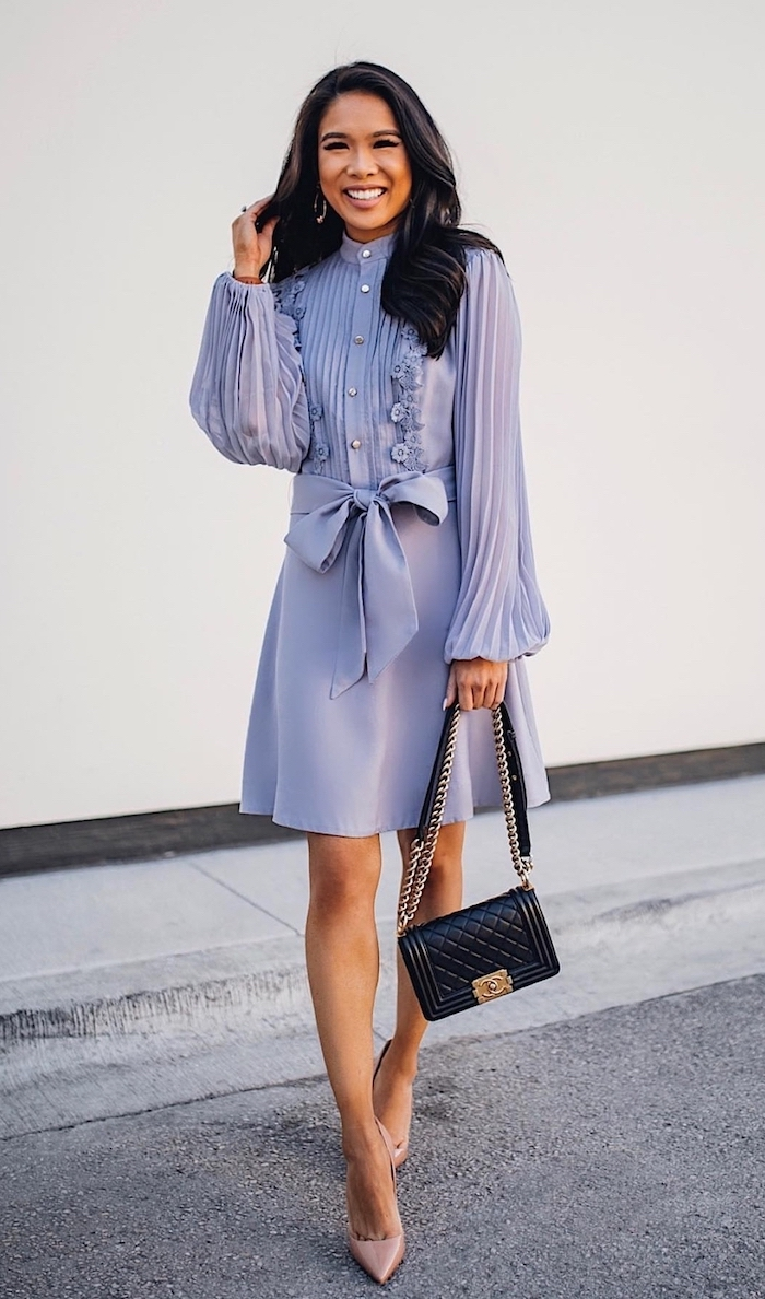 woman with wavy black hair wearing shirt purple dress with long pleated sleeves nude shoes black leather bag dresses to wear to a summer wedding