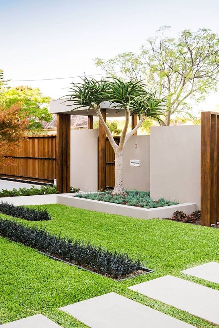 wooden fence with gate tree planted right next to it simple landscaping ideas tiled pathways surrounded by grass and flower beds