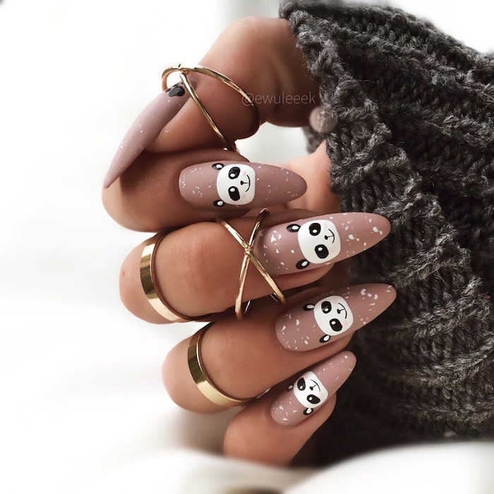 beige nude nail polish with white panda decorations on each nail short nail designs long almond nails gold rings on each finger