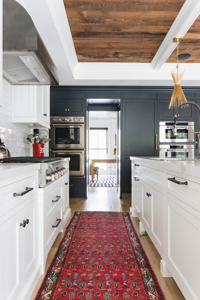 black cabinets on one side white cabinets white subway tiles backsplash rustic farmhouse kitchen colorful carpet on wooden floor
