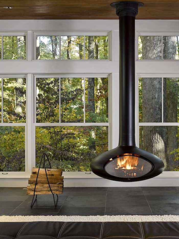 black fireplace hanging from the ceiling black tiled floor screened in back porch small stand for chopped wood on the side