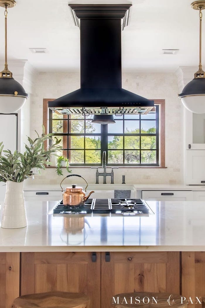 black fixtures above wooden island with white countertop modern farmhouse kitchen decor white tiles on the wall