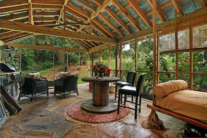 black garden chairs black bar stools around wooden table screened in patio with cathedral ceiling stone floor