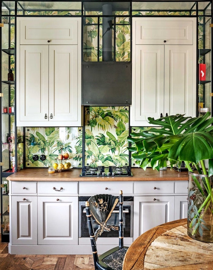 black metal chair next to wooden table kitchen backsplash ideas white wallpaper with green leaves on the wall behind stove with white cabinets wooden countertop