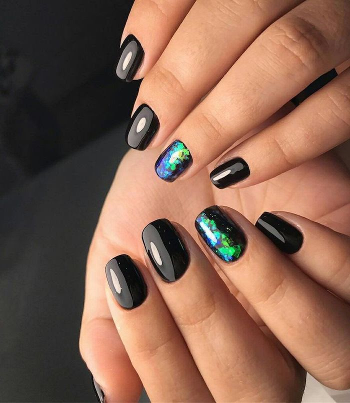 black nail polish multi colored nails green blue purple decorations on ring finger on each hand short squoval nails
