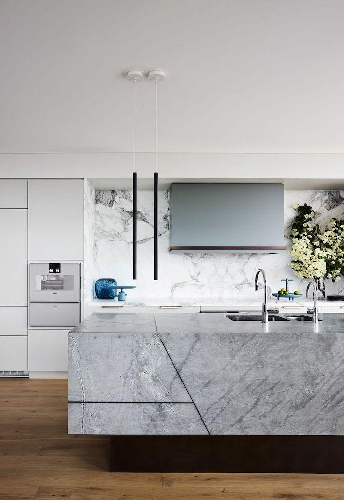 black pendants hanging from the ceiling above granite kitchen island subway tile backsplash marble backsplash white cabinets