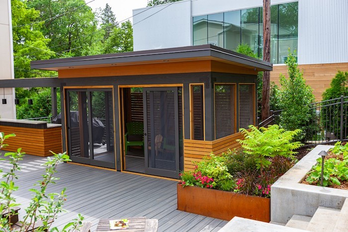 black window frames wooden floor green wooden armchairs inside surrounded by flower beds diy screened in porch