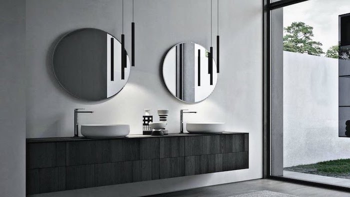 black wooden floating cabinet with two sinks two round mirrors above them small bathroom designs with shower gray wall tall windows