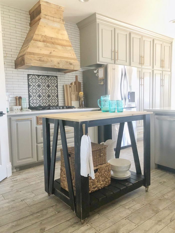black wooden kitchen island farmhouse kitchen backsplash with white tiles light gray cabinets wooden floor