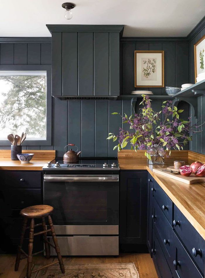 black wooden wall dark blue cabinets drawers farmhouse white kitchen cabinets wooden countertop and floor open shelving
