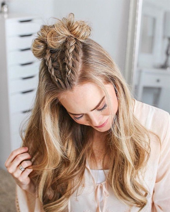 blonde woman with highlights two braids on top ending with two small buns cute easy hairstyles for school rest of hair flowing wavy