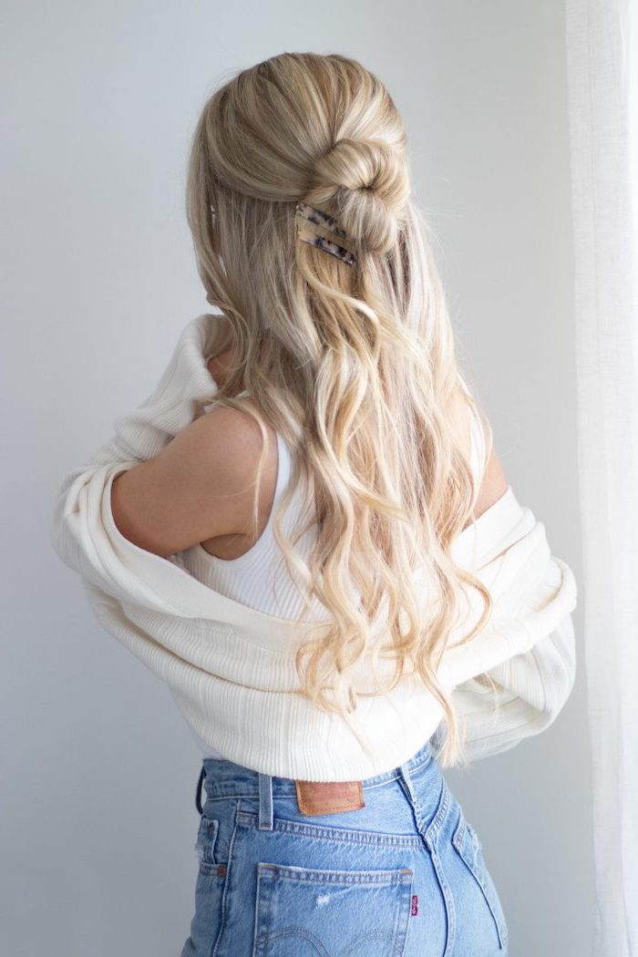 blonde woman with long wavy hair half uf it in a bun cool hairstyles for girls wearing white top cardigan jeans
