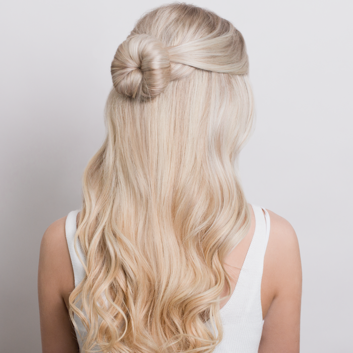 blonde woman with long wavy hair wearing white top easy hairstyles for long hair half of the hair tied in a small bun