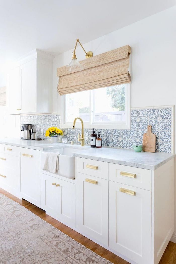 blue and white patterned tiles above the sink backsplash tile ideas white cabinets with marble countertops wooden floor