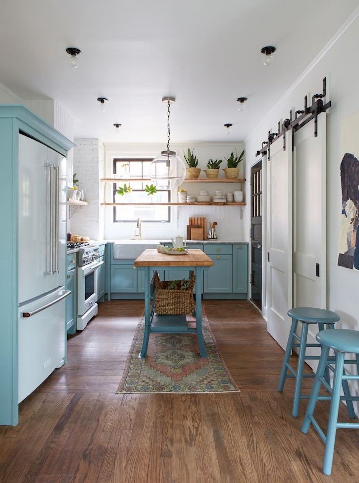 blue cabinets and kitchen island with wooden countertop farmhouse kitchen decor ideas dark wooden floor white brick walls