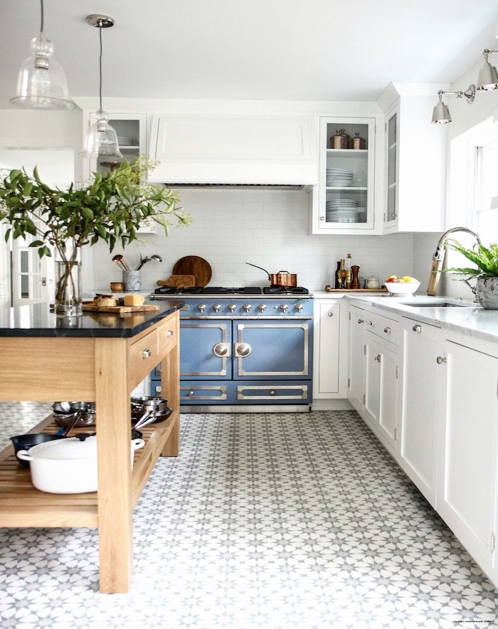 blue stove farmhouse white kitchen cabinets wooden kitchen island with open shelves black countertop black and white patterned tiled floor