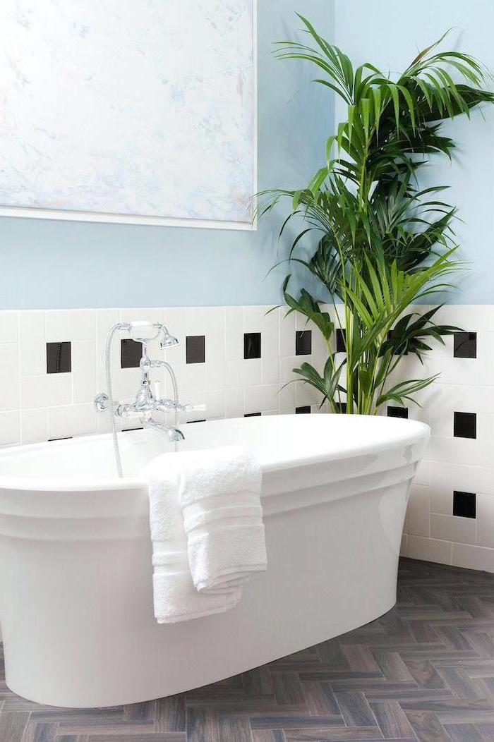 blue wall with white and black tiles bathroom ideas photo gallery wooden floor white bathtub large plant in the corner