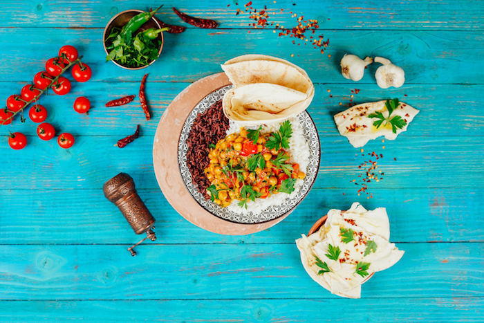 blue wooden surface chickpea curry placed on it in black and white bowl how to cook chickpeas naan bread on the side