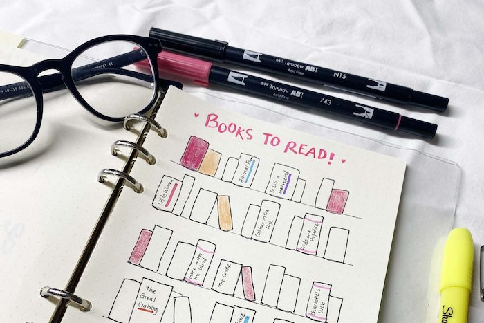 books to read spread with books drawn on the white notebook bullet journal pinterest glasses and markers around it
