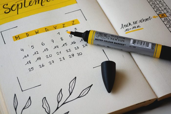 bullet journal themes calendar for september written in black and colored in yellow on white notebook