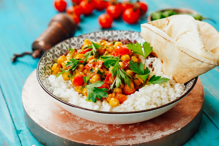 chickpea curry being served with white rice and naan bread in black and white bowl how to cook chickpeas blue wooden surface