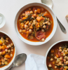 chickpea soup with carrots onion spinach what are chickpeas poured in white ceramic bowls placed on white surface