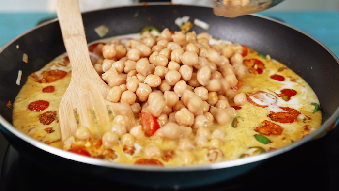 chickpeas being added into saucepan chickpea recipe milk cherry tomatoes jalapeno onion cooking in saucepan with wooden spatula
