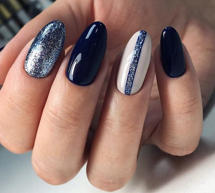dark blue nail polish blue glitter on index finger white nail polish on ring finger cute acrylic nails almond nails
