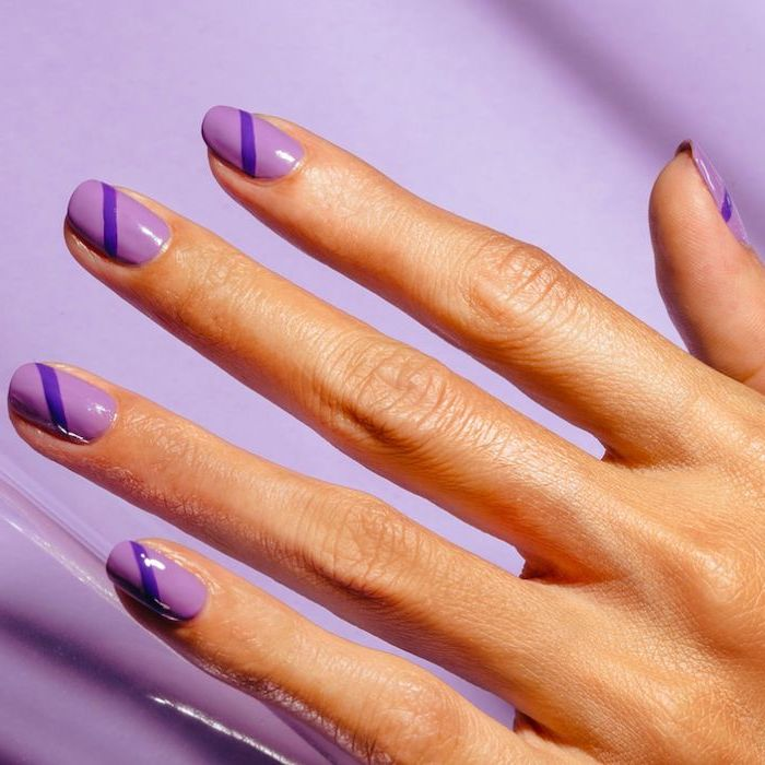 dark purple lines across light purple nail polish multi colored nails short squoval nails purple background