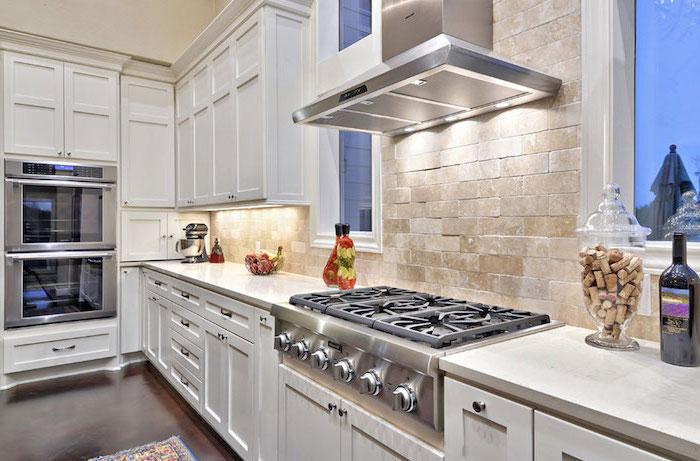 dark wooden floor white cabinets with white countertops subway tile backsplash white bricks for backsplash