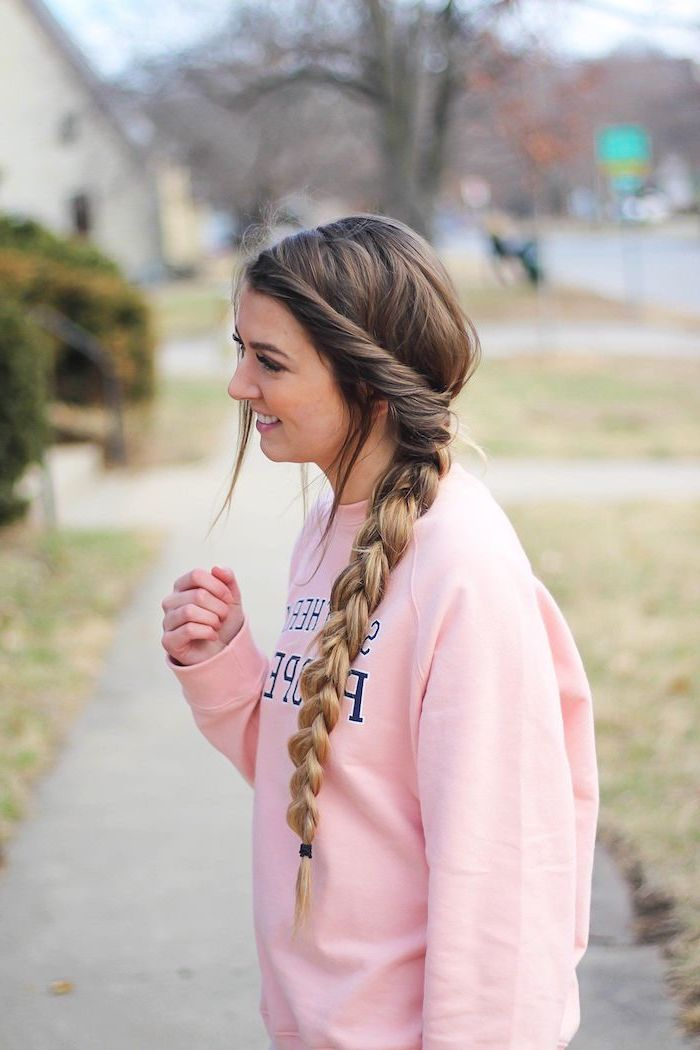 easy hairstyles for long hair brunette girl with blonde ombre hair in long side braid wearing pink varsity sweatshirt