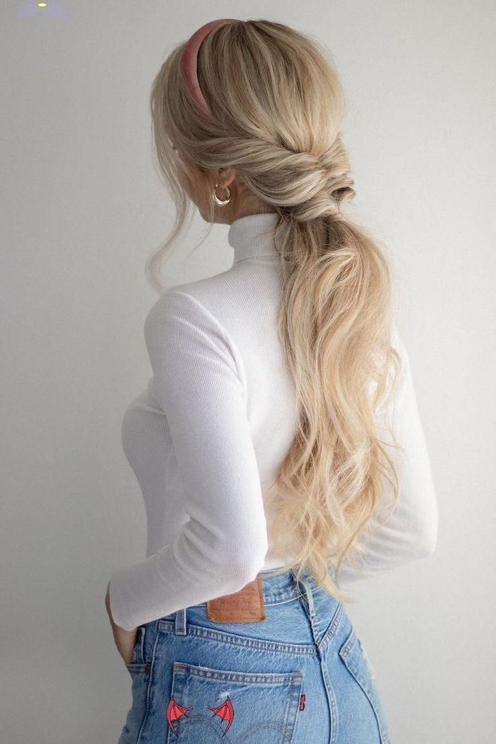 easy hairstyles for short hair woman with long blonde wavy hair half braded in small ponytail wearing white polo blouse jeans