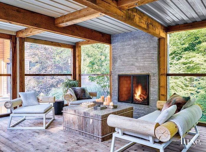 exposed wood beams on ceiling wooden furniture with white cushions colorful throw pillows arranged in front of fireplace enclosed patio ideas wooden floor