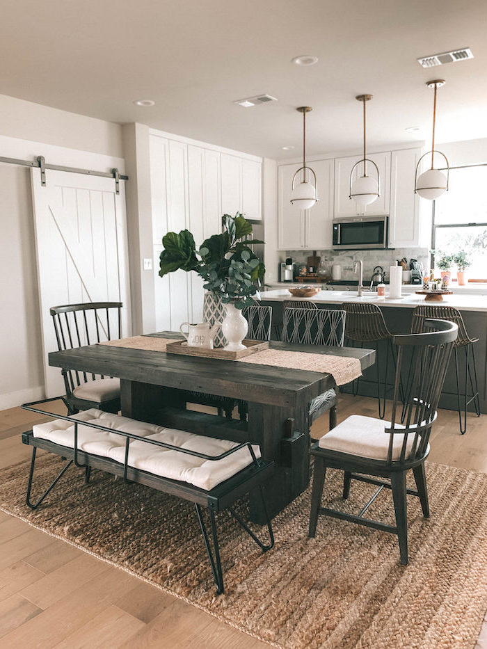 farmhouse white kitchen cabinets dark wooden dining table with bench and wooden chairs black kitchen island wooden floor